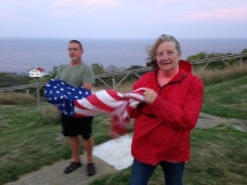 Candy and Bill fold the flag at sunset.